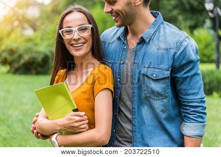 Portrait of joyful girl enjoying hug of her boyfriend. She is looking forward and laughing. Couple is standing in the nature