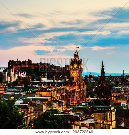 Edinburgh UK. Aerial view from Calton Hill in Edinburgh Scotland. The city with illuminated Castle and Clock Tower at night. Cloudy sunset sky