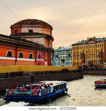 St Petersburg. Old residential buildings and touristic boats at Moyka river in Saint Petersburg Russia. Old main imperial stables in the evening