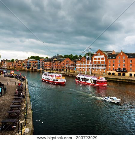 York UK. Embankment area of Ouse river in York UK. Heavy clouds and touristic boats