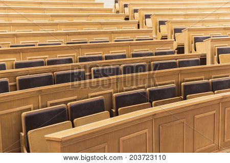 Cozy light lecture hall with wooden desks and comfortable chairs