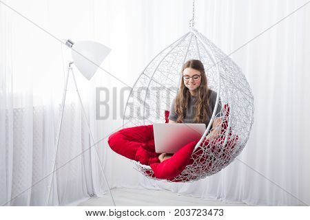 Beautiful woman in eyeglasses in fashionable armchair with laptop. Girl with pc in modern interior at red cushions. Stylish portrait of freelancer, work at home concept