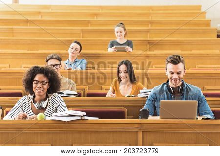 Portrait of joyful young man surfing in internet during lecture. He is sitting near his friends at table in auditorium and laughing. Girl is making notes with joy