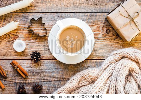 Christmas muffler with cup of cocoa on wooden background top view