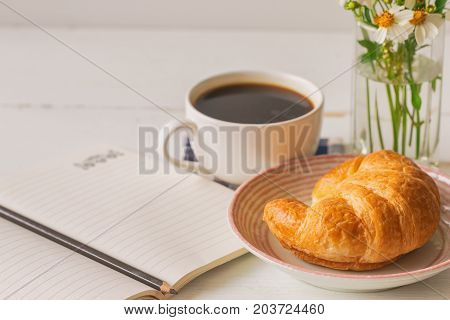 Homemade croissant served with black coffee or americano. Delicious breakfast with fresh croissant and coffee. Croissant and black coffee on wood table with open notebook and pencil with copy space. Coffee and croissant for coffee break.