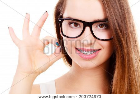 Vision and dentistry problems concept. Happy nerdy teenage wearing big eyeglasses showing her braces on teeth a ok gesture.