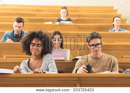 Portrait of cheerful young man and african woman reading book while sitting in lecture hall. They are smiling