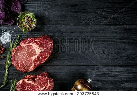 Fresh raw beef with spices, fresh basil and a sprig of rosemary on black wooden background. Top view. Copy space. Still life.. Dry Aged marble beef