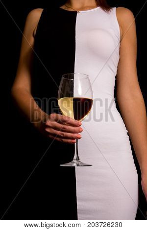 young girl in a black and white dress is holding a glass of white wine in her hands, on which the reflexes are reversed