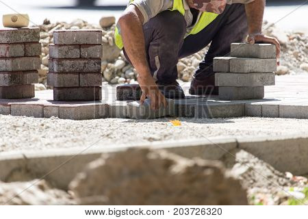 Worker puts sidewalk tile on the road