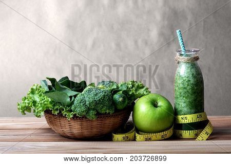 the Healthy fresh green smoothie juice in the glass bottle on wooden table with green apple and vegetables basket for healthy detox and diet habits concept