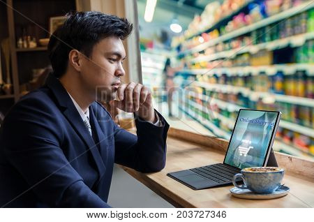 Asian Businessman sitting and using computer laptop showing the shopping online beside the windows glass over the blurred photo of store blur with customer bokeh background Business online shopping concept