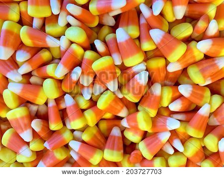 Close up on many candy corn top view looking down. Flat lay. Halloween traditional candy