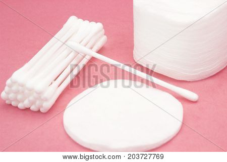 Cotton pads and swabs, bulk of tips. Cotton cosmetic swabs for ear cleaning. Personal care, personal hygiene. Hygienic sanitary swabs on the pink background. Selective soft focus