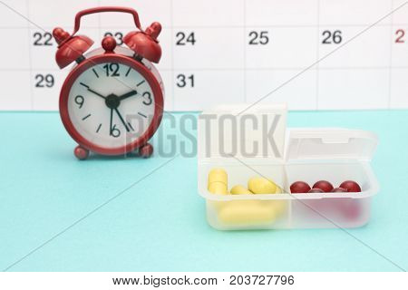 Calendar clocks and yellow pills in pill box. Pharmaceutical tablets and yellow capsules red alarm clock. Medical conceptual photo pharmacy theme. Contraceptive birth control hormone pills