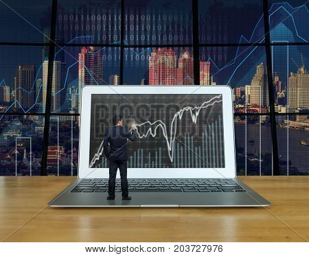 Businessman standing over the computer laptop on the wood table and writing the trading graph at the screen over the blurred photo of trading graph on cityscape background Business trading concept, 3D illustration