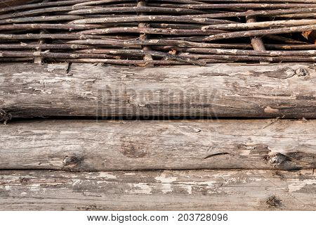 Old wooden wall with logs and wicked twigs