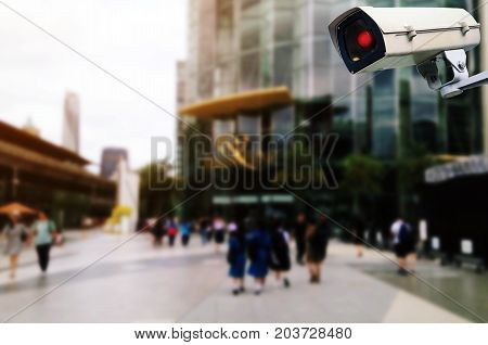 CCTV security outdoor camera system operating with blurred image of people walking at department store shopping center surveillance security and safety technology concept