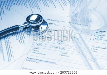 stethoscope test tube beaker and patient information form on desk heart healthcare technology medical diagnosis medical report record history patient concept soft and selective focus blue tone