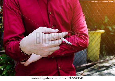 man standing in red shirt and smoking cigarette in the smoking area zone lung cancer smoking cigarette problem no smoking day and world no tobacco day concept
