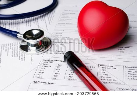 red heart stethoscope blood sample test tube and patient information form on desk heart healthcare technology medical diagnosis heart disease medical report record and history patient concept
