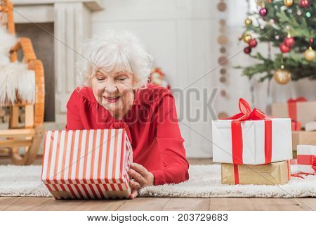 Christmas present. Pleasant senior lady is lying on floor and looking on gift with curiosity. Copy space in the right side