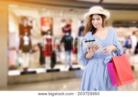 cheerful young asian woman watching special offer in tablet and holding shopping bag while standing at trendy new collection clothes shop in department store shopping mall shopping online concept
