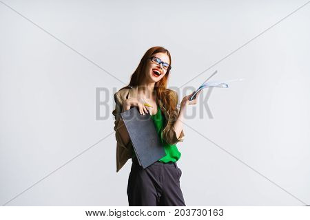Young woman teacher with red hair in glasses laughs, holds a folder with papers, looks at the camera