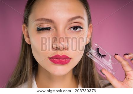 Portrait of a young beautiful woman with false eyelashes. Isolated on a pink background