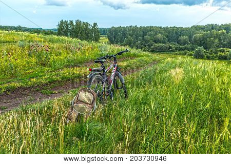 Novosibirsk oblast Siberia Russia - July 10 2017: a Bicycle and backpack on the side of a field road