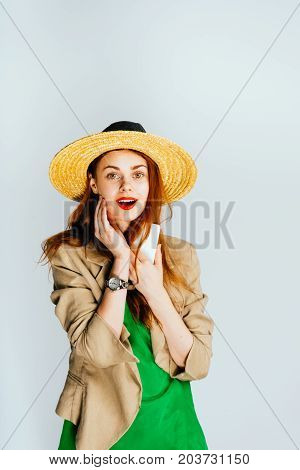 A young beautiful woman in a straw with a wristwatch hat looks surprised at the camera. Isolated on a gray background