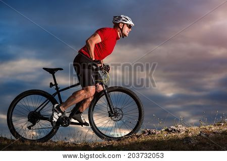 Bike adventure travel photo. Bike tourists ride on the countryside downhill. Autumn sunset on background. Healthy lifestyle concept