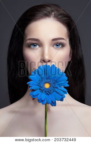 Portrait brunette woman against a dark background blue Flower in hand. Hair care and skin professional makeup. Mysterious bright image of a woman. Sensuality and mystery of women