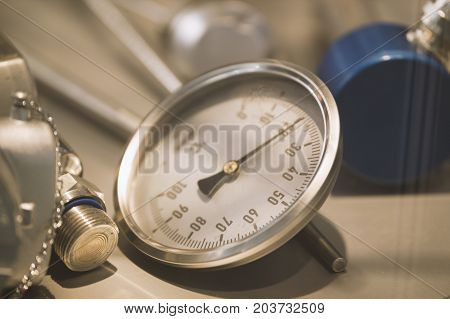 Modern mechanical manometer on extrusion plant - chemistry industry, close up