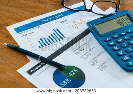 Credit score report on desk with budget calculator pen and glasses