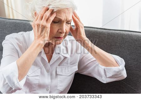 Feeling headache. Aged gray-haired woman is in great pain. She is sitting on sofa and touching her head while expressing suffering