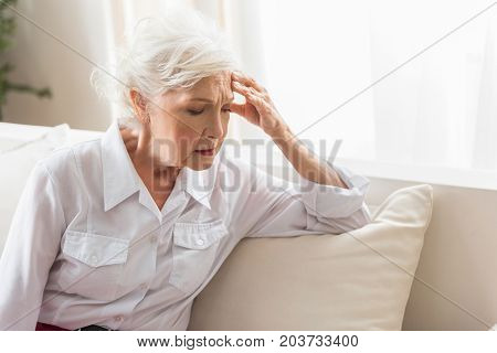 Horrible headache. Senior gray-haired woman is leaning on elbow and touching her head while expressing anguish