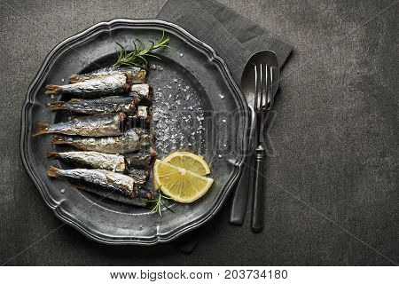 Fried sardines with salt and herbs on rustic background
