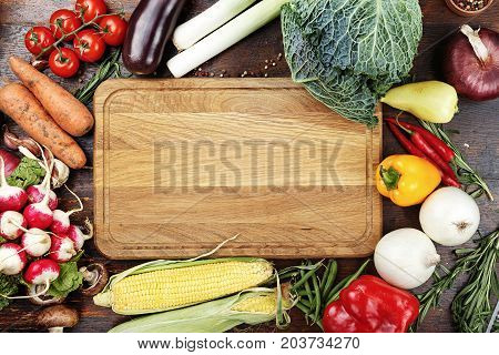 herbs and spices vegetables and sauces on wooden background in the middle of table is cutting bord like a space for text