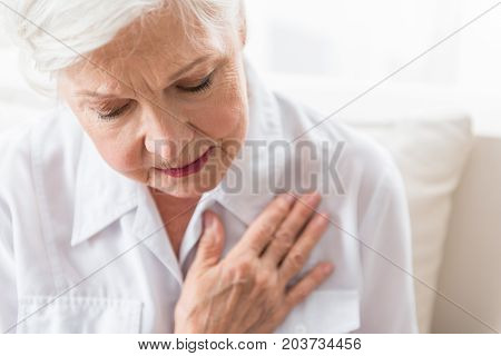 Heartache. Senior cheerless ill woman is touching her chest and feeling bad while suffering from heart attack. Focus on face