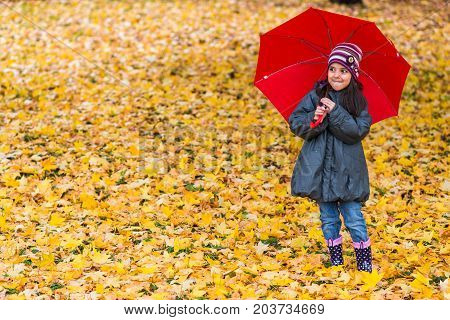 Happy Little Girl Laughing With  Umbrella In The Rain