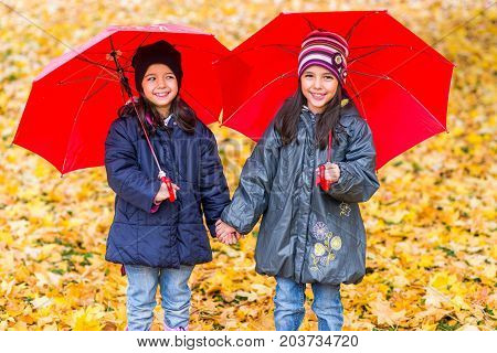 Happy Little Girls Laughing With  Umbrellas In The Rain