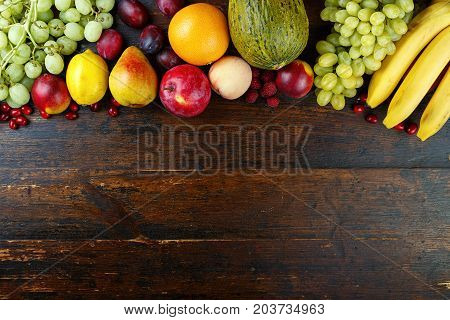 fruit background with exotic fruits on a brown wooden background fruit detox space for text