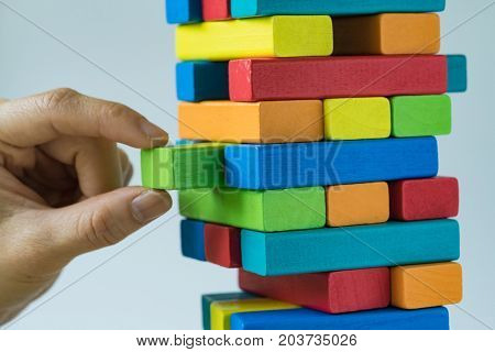 Risk or stability concept as female hand pulling colorful wooden block from the tower.