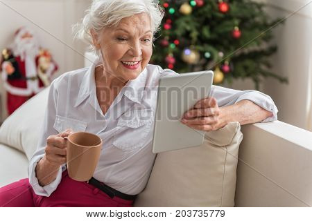 Christmas news. Joyful senior lady is sitting on couch and reading emails on tablet while drinking fresh coffee. She is expressing gladness while resting with Christmas tree on background