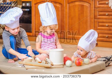 Girl, boy and a newborn baby in chef's hat. Messy fun in the kitchen. Domestic life