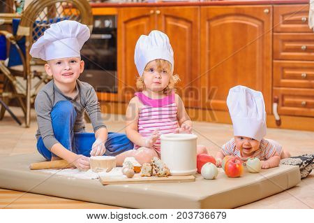 Two siblings - boy and girl - and a newborn kid with them in chef's hats sitting on the kitchen floor soiled with flour playing with food making mess and having fun
