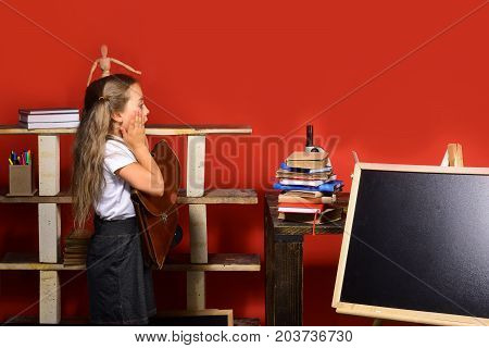 Girl Stands Near Blackboard, Copy Space. Kid And School Supplies