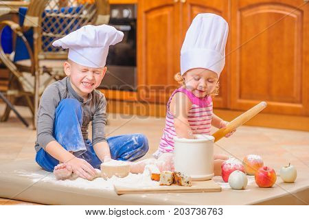 Funtime: two siblings - boy and girl - in chef's hats sitting on the kitchen floor soiled with flour playing with food making mess and having fun