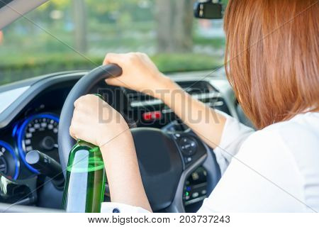 Drunk woman driving and holding a bottle of beer